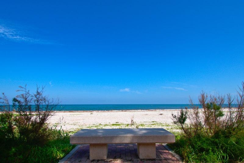 asiento en playa de piedras y mar de fondo